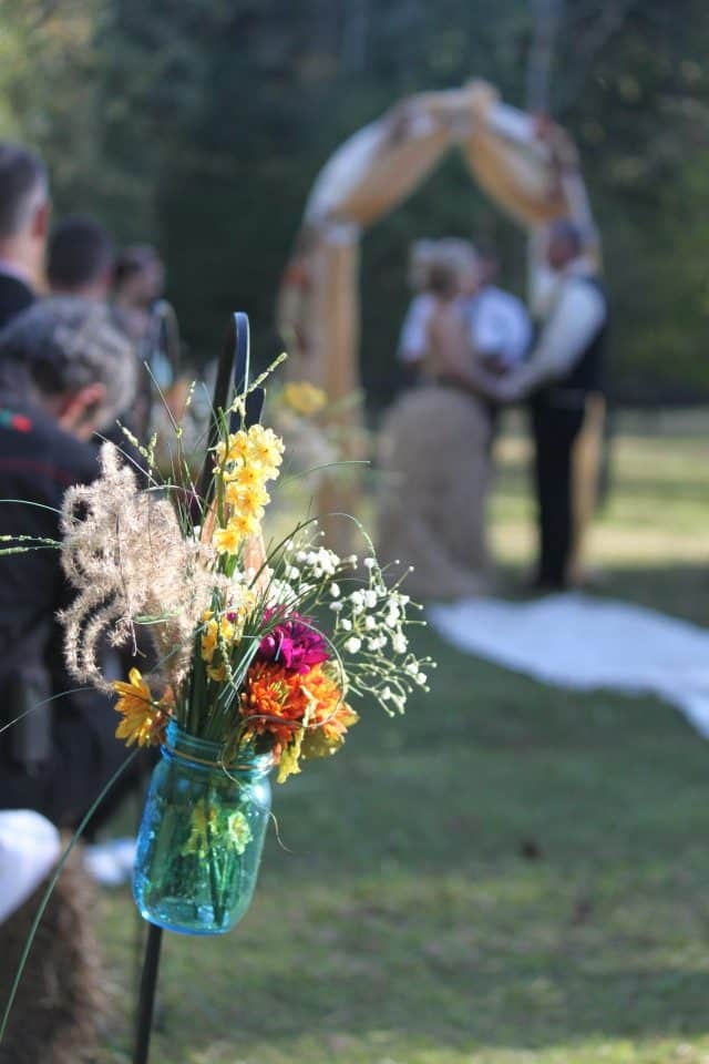 Mason jars with flowers lined the runner to the alter . . . until Dancin' Dan came along!